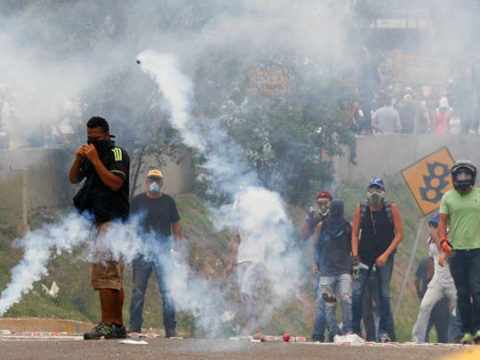 Opponents of President Nicolas Maduro stand amidst tear gas during clashes with security forces in Caracas, Venezuela, Thursday, April 20, 2017. Tens of thousands of protesters flooded the streets again Thursday, one day after three people were killed and hundreds arrested in the biggest anti-government demonstrations in years.