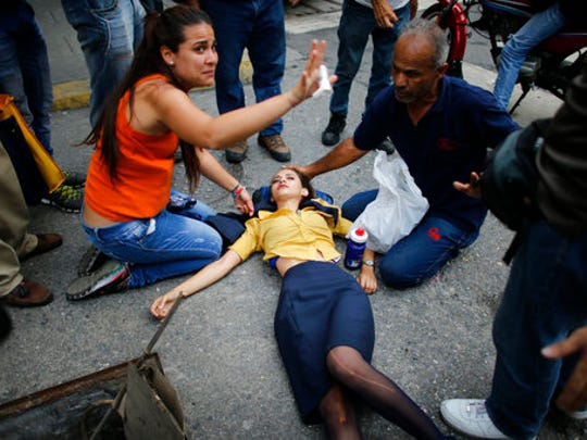 A woman is aided by fellow demonstrators after falling, overcome by tear gas, during anti-government protests in Caracas, Venezuela, Thursday, April 20, 2017. Tens of thousands of protesters asking for the resignation of President Nicolas Maduro flooded the streets again Thursday, one day after three people were killed and hundreds arrested in the biggest anti-government demonstrations in years.