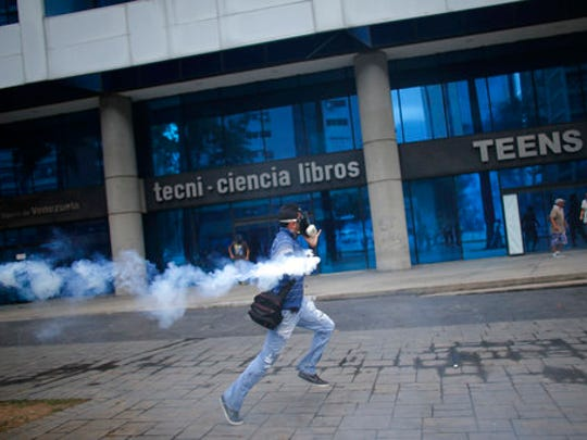 An anti-government protester runs with a canister of tear gas fired by police in Caracas, Venezuela, Thursday, April 20, 2017. Tens of thousands of protesters asking for the resignation of President Nicolas Maduro flooded the streets again Thursday, one day after three people were killed and hundreds arrested in the biggest anti-government demonstrations in years.