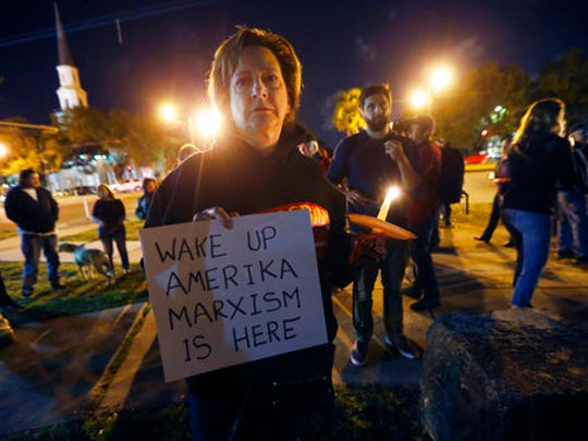 Dana Farley, of New Orleans, participates in a candlelight vigil at the statue of Jefferson Davis in New Orleans, Monday, April 24, 2017. New Orleans will begin taking down Confederate statutes, becoming the latest Southern body to divorce itself from what some say are symbols of racism and intolerance.