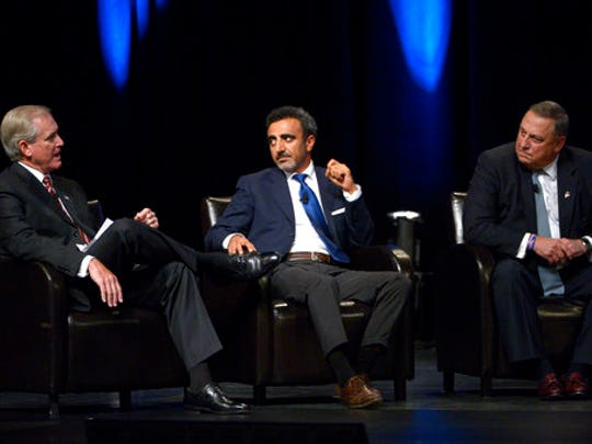 FILE- In this Aug. 22, 2013, file photo, Maine Gov. Paul LePage, right, and Chobani Founder and CEO Hamdi Ulukaya, center, listen as Hampton Products International Chairman and CEO H. Kim Kelley answers a question during a panel discussion in Orlando, Fla. Greek yogurt giant Chobani is suing right-wing radio host Alex Jones, accusing the conspiracy theorist of publishing false information about the company. Chobani filed the lawsuit Monday, April 24, 2017.