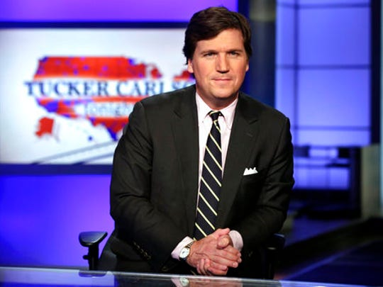 "FILE - In this March 2, 2017 file photo, Tucker Carlson, host of ""Tucker Carlson Tonight,"" poses for photos in a Fox News Channel studio, in New York. Fox News Channel says ""Tucker Carlson Tonight"" will begin airing an hour earlier to fill the time slot vacated by Bill O'Reilly, who lost his job Wednesday after allegations that he sexually harassed women."