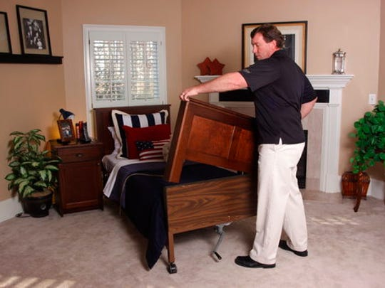 This photo provided by Greg Verlander of TenderCare Beds shows Verlander placing a custom footboard designed to fit over a hospital bed. He started TenderCare Beds as a way to bring more normalcy to people who require a hospital bed for sleeping.