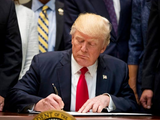 President Donald Trump signs the Education Federalism Executive Order during a federalism event with governors in the Roosevelt Room of the White House in Washington, Wednesday, April 26, 2017.