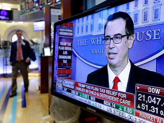 Treasury Secretary Steven Mnuchin appears on a television screen on the floor of the New York Stock Exchange, Wednesday, April 26, 2017. President Donald Trump proposed dramatic cuts in the taxes paid by corporations big and small Wednesday in an overhaul his administration says will spur economic growth and bring jobs and prosperity to America's middle class.