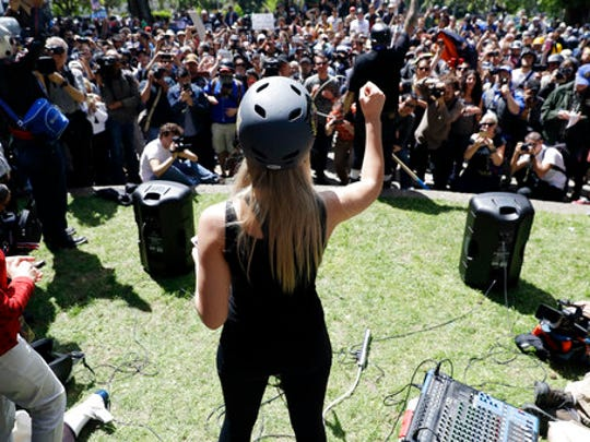 Lauren Southern wears a protective helmet as she speaks during a rally for free speech Thursday, April 27, 2017, in Berkeley, Calif. Demonstrators gathered near the University of California, Berkeley campus amid a strong police presence and rallied to show support for free speech and condemn the views of Ann Coulter and her supporters.