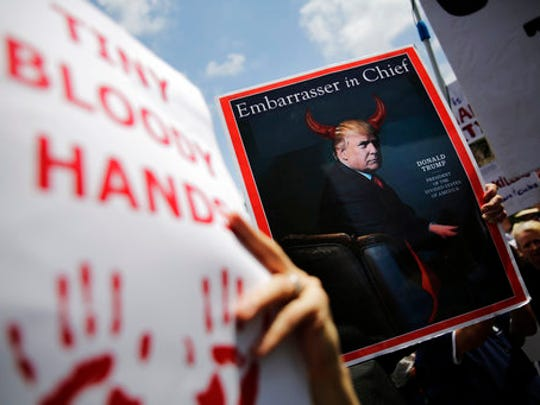 Demonstrators hold signs during a protest outside the National Rifle Association annual convention where President Donald Trump is scheduled to speak in Atlanta, Friday, April 28, 2017.