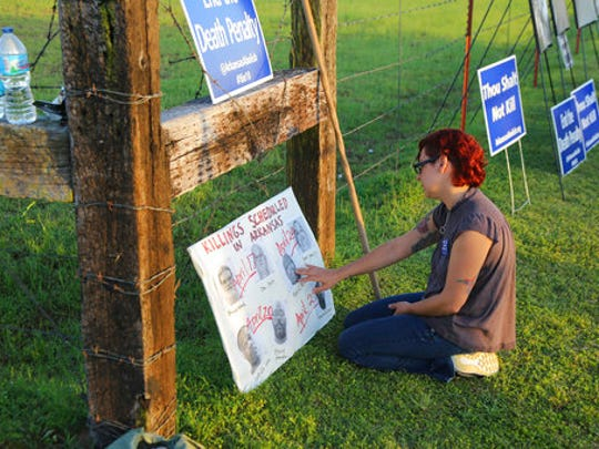 In this Monday, April 24, 2017 photo, Gina Grimm, daughter of inmate Jack Jones, touches a poster of those condemned to be executed outside the Varner Unit near Varner, Ark. Jack Jones and Marcel Williams received lethal injections on the same gurney Monday night, just about three hours apart. It was the first double execution in the United States since 2000.