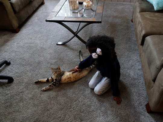 The daughter of LaToya Johnson pets the family cat at their home Friday, April 28, 2017, in San Diego. Johnson says her daughter was fondled in an elementary school bathroom by other students. It's one of thousands of cases student-on-student sex assault in K-12 AP found in a yearlong investigation.