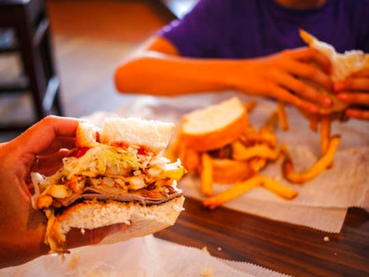In this Aug. 28, 2016 photo, a hungry traveller eats a sandwich filled with french fries and cole slaw at Primati Bros. Restaurant and Bar, in Pittsburgh, Penn. The original location in Pittsburgh's Strip District opened in 1933.