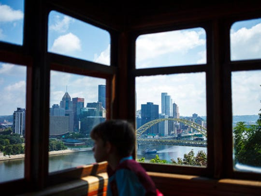 In this Aug. 29, 2016 photo, downtown Pittsburgh is seen through the window of the Duquesne Incline in Pittsburgh, Penn. The incline opened in 1877 and was restored in 1963.