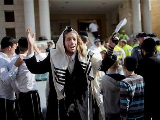 An ultra-Orthodox Jewish man prays as Israeli rescue