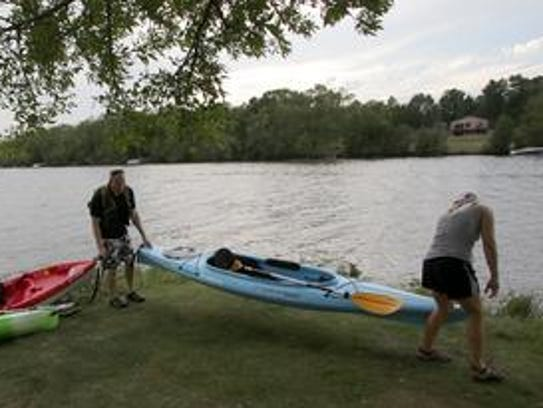 Kayakers take care of their boats after paddling on