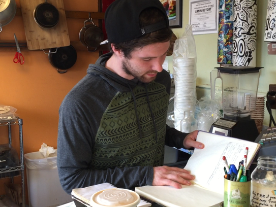 Wildflower earthy vegan fare employee Seth Beatty checks