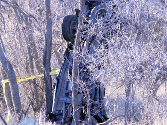 A vehicle was upside down leaning on a tree at the