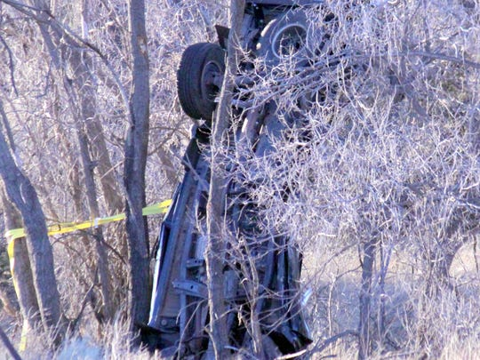 A vehicle was upside down leaning on a tree at the crash site.