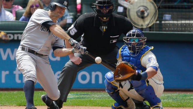 New York Yankees' Brett Gardner hits a lead-off home run as Seattle Mariners catcher Carlos Ruiz and home plate umpire Tom Woodring look on in the first inning of a baseball game, Sunday, July 23, 2017, in Seattle. (AP Photo/Ted S. Warren)