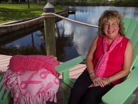 """Luanne Holmes of Cape Coral has recovered from breast cancer and is a speaker and very pro-active in bringing awareness. She owns a few blankets in recognition of breast cancer awareness. """"I feel great comfort wehenever I use them."""""""