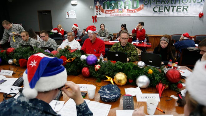 Volunteers take phone calls from children asking where Santa is and when he will deliver presents to their homes, inside a phone-in center during the annual NORAD Tracks Santa Operation, at the North American Aerospace Defense Command at Peterson Air Force Base, Colo., on Wednesday, Dec. 24, 2014. Hundreds of military and civilian volunteers at NORAD are estimated to field more than 100,000 calls this year throughout Christmas Eve, from children from all over the world eager to hear about Santa's progress.