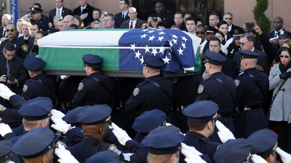 Pallbearers carry the casket of New York City police