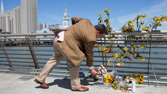 A mourner lays down flowers following a vigil for Kathryn Steinle on July 6, 2015, on Pier 14 in San Francisco. Steinle was gunned down while out for an evening stroll at Pier 14 with her father and a family friend on July 1.