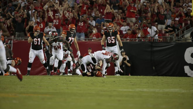 Cincinnati Bengals quarterback Andy Dalton (14) is sacked in the first quarter of the NFL pre-season game between the Cincinnati Bengals and the Tampa Bay Buccaneers at Raymond James Stadium in Tampa, Fla., on Monday, Aug. 24, 2015.