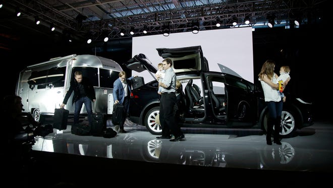 Elon Musk, CEO of Tesla Motors Inc., at left, shows the amount of cargo space and towing capacity of the new  Model X
