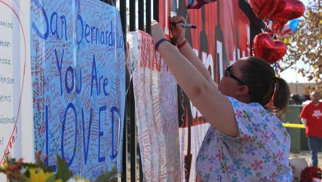 Bonnie Lehman, 26, of Fontana, steps up Monday to sign a memorial for the San Bernardino shooting victims.