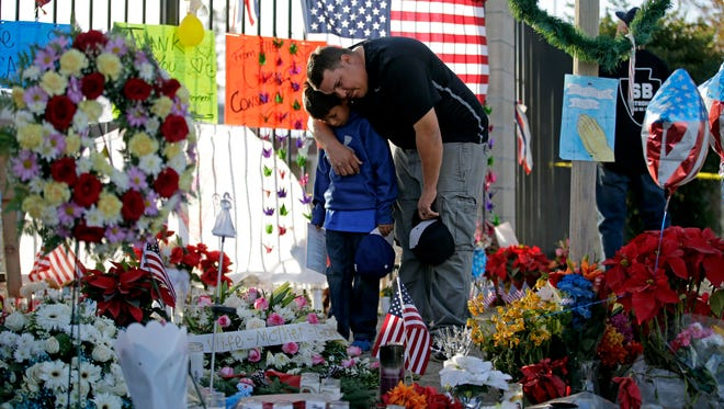 "In this Dec. 7, 2015 file photo, Gary  Mendoza, and his son Michael pay their respects at a makeshift memorial site honoring shooting victims, in San Bernardino, Calif. Hughes Springs, Texas Police Chief Randy Kennedy, who warned President Barack Obama that he would ""cause a revolution in this country"" if Obama tries to disarm Americans, has joined a growing number of law enforcement officials urging people to arm themselves against Islamic extremists."