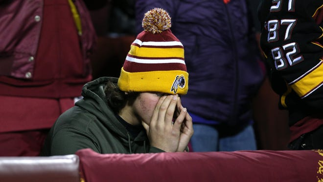 A Washington Redskins fan covers his face during a game against the Dallas Cowboys at FedExField on Dec. 7.