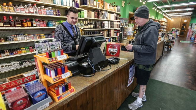 Jeff Ayers (right) purchases Powerball tickets from David Richmond-Jones, assistant manager at 21st Amendment Liquors in Broad Ripple, on Friday, Jan. 8, 2015.