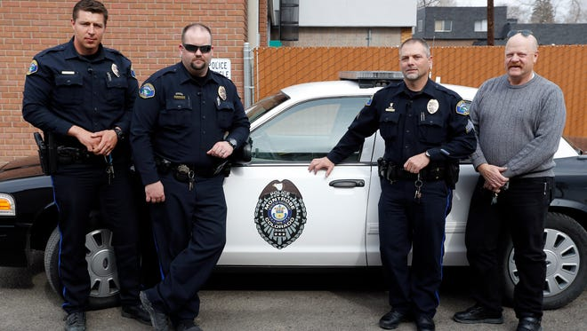 In this Feb. 23, 2016 photo, Police Commander Keith Caddy, right, stands with fellow local police officers, in Montrose Colo, where suicide rates are among the highest in the nation. Caddy has been around guns since childhood as a hunter, lawman, firearms instructor and licensed gun seller. Now he's doing outreach for the Gun Shop Project, and most of the businesses he has visited agreed to display the suicide-awareness materials once they were assured it wasn't a gun-takeaway program in disguise.