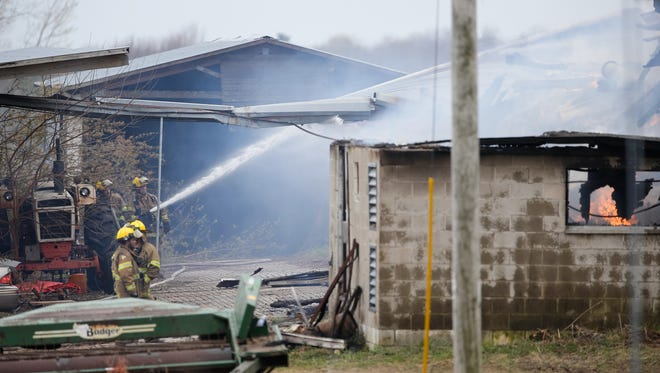 Firefighters work the scene of a barn fire along State 96 near Dale.