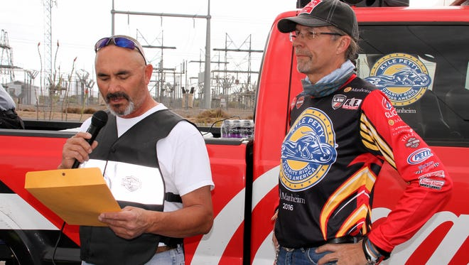 City of Deming Mayor Benny Jasso reads the Charity Ride Across America Day Proclamation as former NASCAR driver and Ride founder Kyle Petty listens along with 300 NASCAR fans on Sunday at the 5R Travel Center located north of Deming on U.S. Highway 180 (Silver City Hwy.).