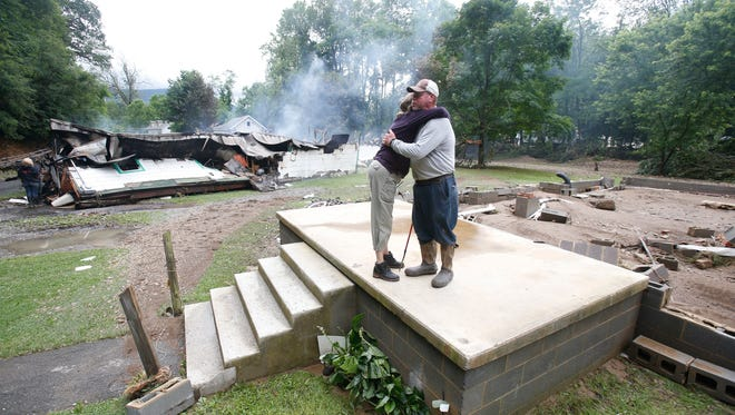 Jimmy Scott gets a hug from Anna May Watson, left, as they clean up from severe flooding in White Sulphur Springs, W. Va., June 24, 2016. Scott lost his home to the flood and a fire that consumed his and the homes of several relatives.