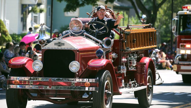 A vintage firetruck from the Penfield Fire Department takes part in the Fairport July 4th parade.