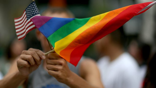A protester holds an American flag and rainbow flag in 2014 in support of marriage equality.