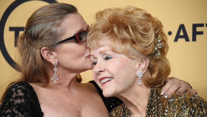 Carrie Fisher gives a kiss to her mother,  Debbie Reynolds, in the photo room of the 20th Screen Actors Guild Awards in January 2015.