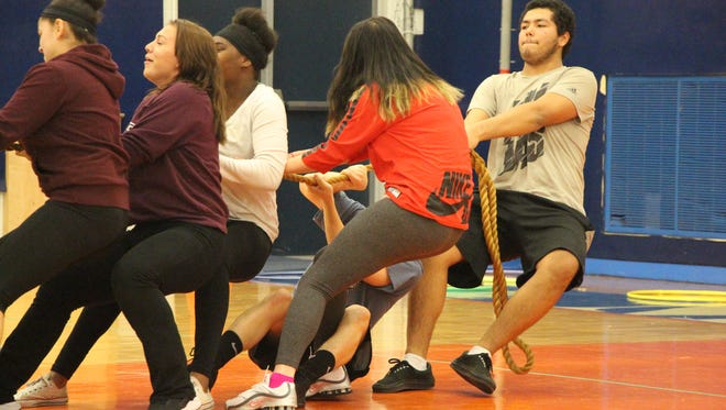 Millville Memorial High School students play tug of war as part of the traditional holiday games.