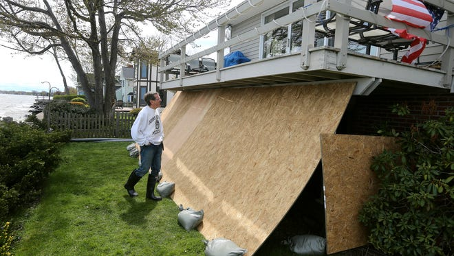 Bill Joyce, who lives on Old Edgemere Drive, used plywood to protect his house from damaging wave action from Lake Ontario.  Joyce has suffered flooding and break wall damage.