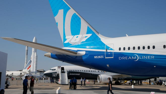 A man walks past a Boing 787-10 Dreamliner on June 18, 2017, ahead of the official opening of the Paris Air Show.