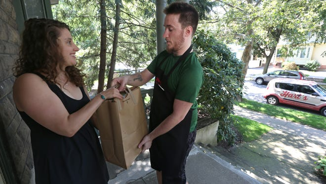 Sam Dubay, a personal shopper with Hart's Local Grocers, delivers groceries to customer Anna Rosensweig, at her Park Avenue home Wednesday, Aug. 2, 2017.