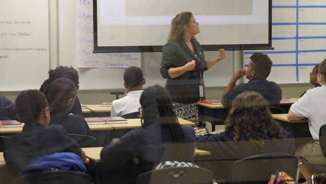 "Middle school students at Governor's Charter take notes during a lesson. The school's classrooms, which have glass walls, are grouped by grade level in ""pods"" and share a common meeting area."