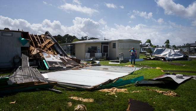 Richard Klubb, 69, assesses the damage caused by Hurricane Irma in the Tahiti Mobile Village in Estero on Monday, Sept. 11, 2017.