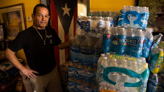 Wesley Andujar, owner of Puerto Rico Latin Bar and Grill, stands next to donated beverages at his restaurant that will be sent to Puerto Rico.