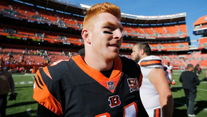 """Cincinnati Bengals quarterback Andy Dalton (14) smiles at midfield after the NFL Week 4 game between the Cleveland Browns and the Cincinnati Bengals at FirstEnergy Stadium in downtown Cleveland on Sunday, Oct. 1, 2017. The Bengals tallied their first win of the season, 31-7, in the """"Battle for Ohio"""" game."""