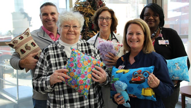 Members or the PRMC Women's and Children's division join Judy Young and her son-in-law Todd Jonischek to celebrate Judy's 20th and final year of handcrafting pillows for young patients in Pediatrics and the Emergency Department.