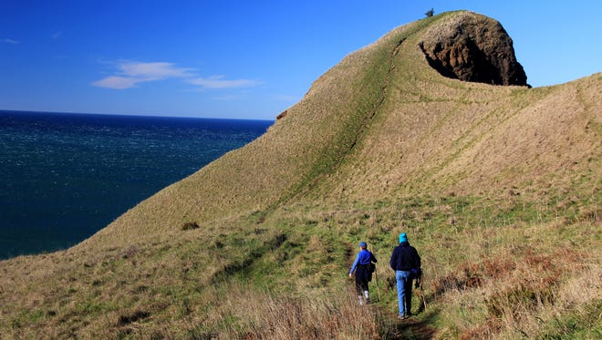 Two hikers make their way toward the summit of God's Thumb, on the north end of Lincoln City.