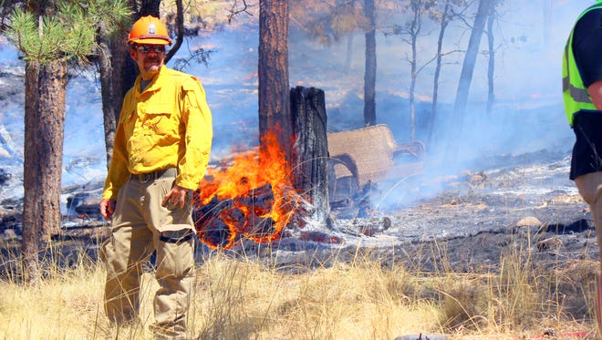 A firefighters checks out a burn area at the College Fire in Ruidoso.