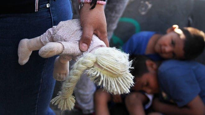 A Mexican woman holds a doll next to children at the Paso Del Norte Port of Entry, at the U.S.-Mexico border in Chihuahua state, Mexico on June 20, 2018.